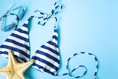 Blue swimsuit, sunglasses and starfish on blue background. Beach background concept stock image