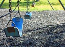 Blue swings. Empty blue swings in a park setting Royalty Free Stock Photo