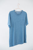 Blue t-shirt with pocket hanging on hanger Stock Photos