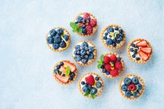 Blue table decorated of sugar powder with variety berry tartlets or cake top view. Tasty pastry desserts. royalty free stock images