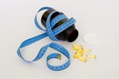 Blue Tape Measure Wrapping Black Medication Pill Bottle With White Cap Stock Photo