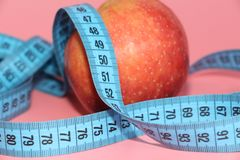 Blue tape for measuring the body around an apple. Apple on a pink background. The concept of losing weight, diet stock photo