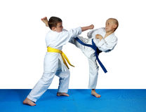 On the blue tatami small athletes are training paired exercises karate. On the blue tatami athletes are training paired exercises karate Stock Images