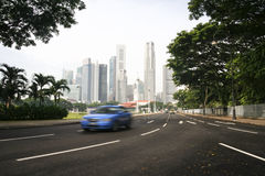 Taxi cab driving through singapore city. Blurred Blue taxi cab driving away from city centre financial district of singapore n multi lane road Stock Photography