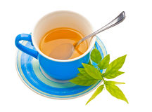 Blue tea cup and green leaves isolated on white Royalty Free Stock Photography