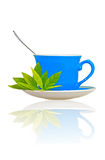 Blue tea cup with green leaves and a spoon Royalty Free Stock Photos