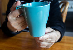 Blue tea cup. In hands of an elderly woman Stock Photos