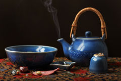 Blue Tea Set Night. An Asian blue celedon teapot, bowl and cup along with various trinkets on a batik cloth with a black background and steam rising from the pot Royalty Free Stock Image