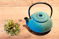 Blue teapot and chamomile plant Royalty Free Stock Image