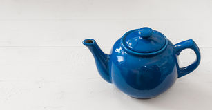 Blue teapot on white wooden background Stock Photography
