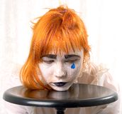 Blue tear. Clown makeup girl with red hair and blue tear royalty free stock photo