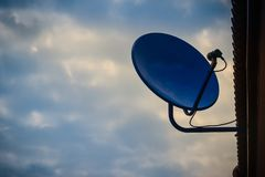 Blue telecommunication TV dish with receiver against clouds and Stock Image
