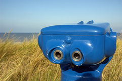 Blue telescope on the beach. In Bergen aan Zee, Netherlands. In the back the North Sea and the blue sky on a wonderful sunny day stock photography