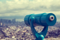 Blue telescope and blurred city on background. Royalty Free Stock Images