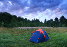 Blue tent in a forest and cloudy sky Stock Photo