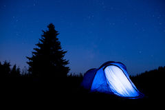 Blue tent night sky pine tree. Blue illuminated tent with travelers in the mountain. Background of a pine tree silhouette and the starry summer night sky Royalty Free Stock Photography