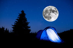 Blue tent night sky pine tree Super Moon. Super Moon. Blue illuminated tent with travelers in the mountain. Background of a pine tree silhouette and the starry Stock Photography