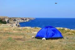 Blue tent on the rocky seashore. Bird flying high Stock Photo