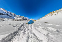 Blue tent in the snowy peaks of the mountains. Wide-angle panorama Stock Photo