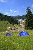 Blue tents at mountain fairground. Blue tents on meadow at the foreground and fairgound at the backdrop of beautiful scenery of Rhodope Mountains near the Royalty Free Stock Image