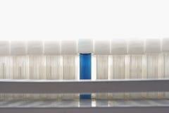 Blue test tube amongst empty test tubes Stock Images