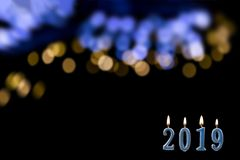 Blue text of 2019 lit candle with flame over shinny blurry blue gold, on black wall. New year concept. background, royalty free stock photo
