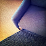 Blue textile armchair and knitted carpet Royalty Free Stock Photo