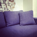 Blue textile sofa near brick wall Royalty Free Stock Image