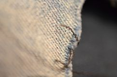 Blue texture maden from a piece of jeans with torned hole with threads blurred toned. royalty free stock images