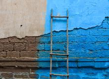 Blue textured brick wall with ladder royalty free stock image