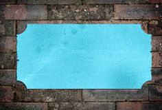 Blue textured label with frayed edges. On brick wall Royalty Free Stock Photos