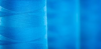 Blue textured web banner background, Close-up bobbins with blue colored thread for industrial textile machines.  Royalty Free Stock Photos