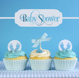 Blue theme baby boy cupcakes with greeting sample text. In vintage style frame for baby shower or new born nursery greeting card concept stock photo
