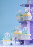 Blue theme baby boy cupcakes on purple polka dot cupcake stand. Against blue background for baby shower or new born nursery greeting card concept stock images