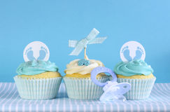 Blue theme baby boy three cupcakes. Against blue background for baby shower or new born nursery greeting card concept stock photos