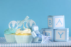 Blue theme baby boy three cupcakes and baby favour gift boxes. Against blue background for baby shower or new born nursery greeting card concept stock photos