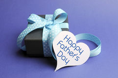 Happy Fathers Day blue theme gift and message on heart tag. Blue theme black box present gift with polka dot ribbon and white heart shape tag with Happy Fathers Stock Photo