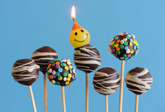 Blue theme chocolate cake pops. Celebratory dark chocolate kiddy cake pops with a birthday candle against a deep blue background Stock Photo