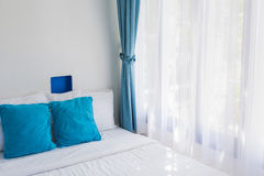Blue theme pillows white bedroom light curtain Royalty Free Stock Image