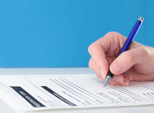 Blue Themed Pen in Hand Completing Form Royalty Free Stock Image