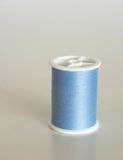 Blue thread. Bobin of blue thread on grey background Royalty Free Stock Images