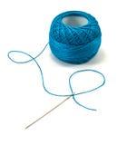 Blue thread ball and needle Royalty Free Stock Photos