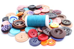 Blue thread with needle and collection of colored sewing buttons Royalty Free Stock Images