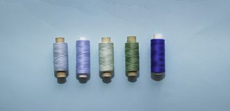 Blue thread reels for sewing on a blue background. Concept of blue, green sewing, needlework, handmade. Use for backgrounds, wallpapers, posters stock images