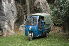 Blue three-wheeled transport vehicle in the Stone Forest. Kunming, Yunnan, China royalty free stock images