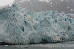 Blue Tidewater Glacier. Massive Blue Glacier with Gray Mountains in the Background Stock Photo