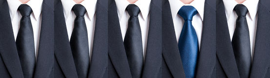 Blue tie between black neckties. As stand out of the pattern or crowd concept Royalty Free Stock Photography