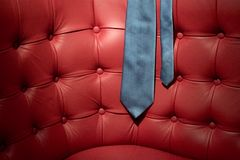 Blue tie on red leather couch Royalty Free Stock Photography