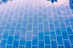 Blue tiled floor of a pool under clear water. In which the sky is reflected Stock Photography