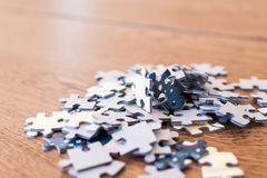 blue tiles of a puzzle on a wooden table. Concept to indicate le royalty free stock image